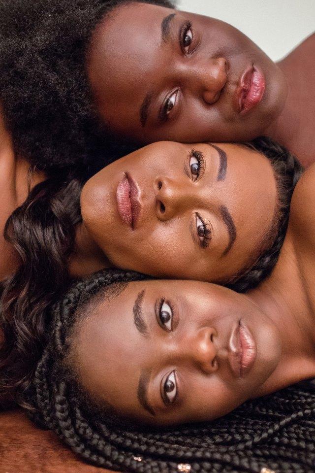 Trois visages  de femmes de carnation noire, regardant l'objectif à la verticale